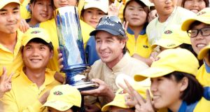 Brett Rumford of Australia (centre) holding the winner's trophy  with caddies after winning the final round of the Volvo China Open at 2013 Binhai Lake Golf Course  in Tianjin, China. Photograph: by Lintao Zhang/Getty Images
