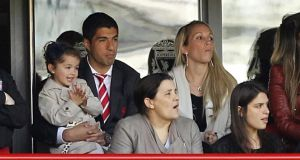 Liverpool's Luis Suarez  watches the Merseyside derby from the stands with his wife and daughter at Anfield. Photograph: Peter Byrne/PA Wire