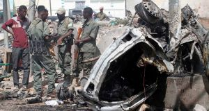 Officers stand by the remains of a wrecked car at the scene of car bomb explosion. Photograph: Feisal Omar/Reuters