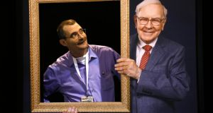 Berkshire Hathaway shareholder Richard Harmon poses in an opening in a wall behind a picture frame held by a photograph of Berkshire chairman Warren Buffet, at the company's annual meeting in Omaha. Photograph: Reuters/Rick Wilking