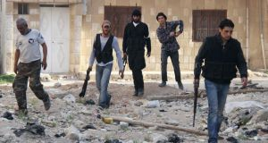 Free Syrian Army fighters carry their weapons while walking down a debris-filled street in the al-Ziyabiya area in Damascus. Photograph: Ward Al-Keswani/Reuters