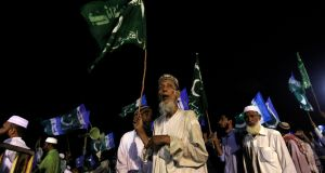 A supporter of the political and religious party Jamaat-e-Islami holds a party flag while listening to the speeches of leaders during an election campaign rally in Karachi yesterday. Elections will be held in Pakistan on Saturday.  Photograph: Reuters/Akhtar Soomro.