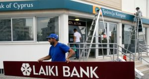 Workers remove signs from a branch of Laiki Bank in Nicosia.  Photograph: Andreas Manolis/Reuters