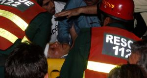 Rescue workers carry Imran Khan, who is chairman of political party Pakistan Tehreek-e-Insaf, after he fell from a makeshift elevator during his election campaign rally in Lahore. Photograph: Mohsin Raza/Reuters.