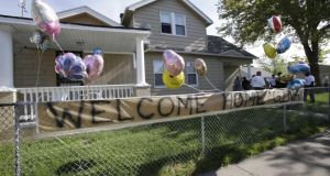 "A ""welcome home""  sign hangs on a fence outside the home of Gina DeJesus. Photograph: AP /Tony Dejak"