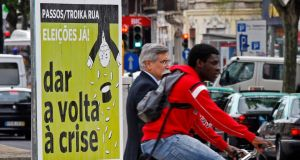 "People pass by a political poster reading:  ""Troika out. Elections now. Turn the crisis around. Cut the debt and not the salaries"", on a street in Lisbon earlier today.  Photograph: Jose Manuel Ribeiro/Reuters"
