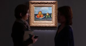 Visitors talk near Paul Cezanne's 'Les Pommes,' during a preview of Sotheby's  Impressionist and Modern Art Evening Sale at Sotheby's in New York. Photograph: Mike Segar/Reuters