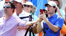 Rory McIlroy takes a picture of his caddie, JP Fitzgerald, playing a shot to the par-three 17th during a tournament for caddies at Sawgrass yesterday. Photograph: Getty Images