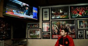 Manchester United fan Christopher Kearney sits in The Red Devil pub on Belfast's Falls road watching the latest developments in the Alex Ferguson retirement story.