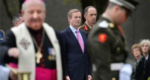 Taoiseach Enda Kenny watches Auxiliary Bishop of Dublin Raymond Field, blessing the graves at the memorial during the annual 1916 commemoration.