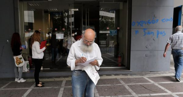 A man checks a document as he leaves a Greek Manpower Employment Organisation  office in central Athens May 9, 2013. Greece's jobless rate rose to 27 per cent in February. Photograph: John Kolesidis/Reuters.