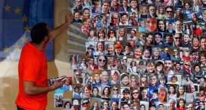 A staff member places photos on a wall showing portraits of European Union citizens outside the EU Commission building during Europe Day 2013 in Brussels. Photograph: Reuters