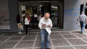 A man checks a document outside an employment office in Athens