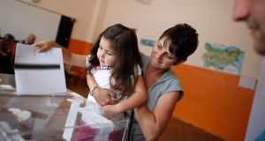 A woman holds her daughter as she casts her vote at a polling station in Sofia today. Stoyan Nenov/Reuters