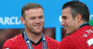 Wayne Rooney of Manchester United celebrates with  Robin van Persie following the presentation of the Premier League trophy at Old Trafford yesterday