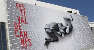 Workers sets up a giant 66th Cannes Film Festival official poster at the front of the Palais des Festivals, showing Paul Newman and Joanne Woodward kissing on the set of  A New Kind of Love  in 1963. The Cannes Film Festival starts today. Photograph: Lionel Cironneau/AP