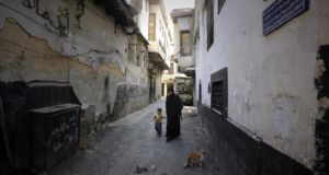 A Syrian woman and her son in an alley in the Old City of Damascus, where an area covering 12 blocks was declared a peace zone in which no fighting was permitted: Photograph: Joseph Eid/AFP/Getty Images