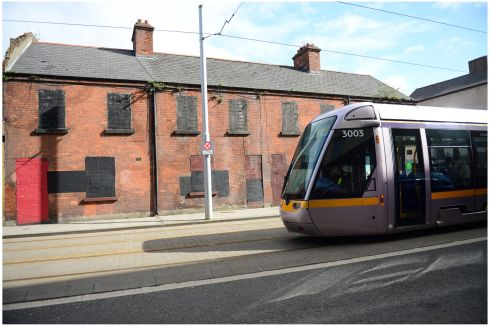 A Luas tram  passes a derelict terrace of redbrick houses on Benburb Street in North inner city Dublin. Photograph: Bryan O'Brien
