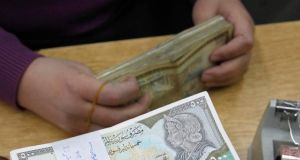 An employee counts Syrian pound notes at the Syrian central bank in Damascus. The Syrian pound has lost about 60 per cent of its value against the US dollar in two years. Photograph: Reuters/Khaled al-Hariri