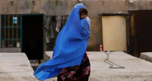 An Afghan woman wearing a burqa carries a child  along a street on the outskirts of Kabul. Photograph: Omar Sobhani/Reuters