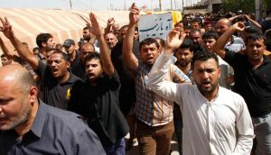 Iraqi mourners chant slogans against the Sunni-dominated Free Syrian Army rebel group and al-Qaida-affiliated Islamist group Jabhat al-Nusra as they carry the coffin of a Shia militia fighter who was killed in clashes with the Free Syrian Army. Photograph: Atef Hassan/Reuters