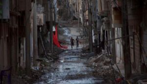 People run down a street in the city of Deir al-Zor, in eastern Syria, Photograph: Reuters/Khalil Ashawi