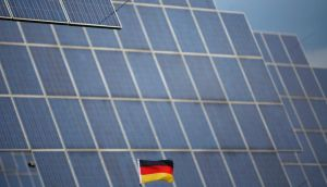 A German national flag  in front of solar panels in Bad Hersfeld. Photograph:  Lisi Niesner/Reuters