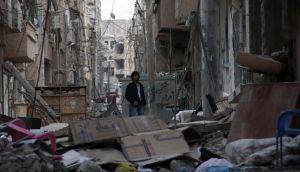 A man stands in a damaged street filled with rubble in Deir al-Zor. Photograph: Khalil Ashawi/Reuters