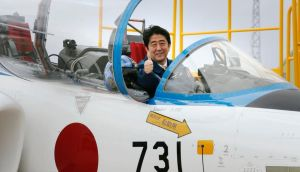 Shinzo Abe poses inside the cockpit of a T-4 training jet. The photograph sparked uproar   in South Korea and China as the number 731 reminded  many of the infamous Japanese bio-warfare Unit 731, which carried out experiments on live prisoners and unleashed a plague on Chinese civilians.  Photograph:  Reuters