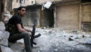 A Free Syrian Army fighter sits on sandbags in the refugee camp of Yarmouk, near Damascus. Photograph: Reuters