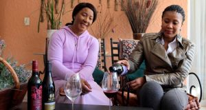Former South African president, Nelson Mandela's daughter Makaziwe Mandela, (left) with her daughter Tukwini   pose with a bottle of House of Mandela wine at their home in Johannesburg. Photograph: Getty Images