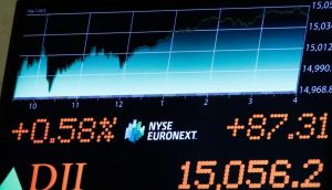 A screen displays a recent  Dow Jones Industrial Average. For the last 18 Tuesdays, the average has risen every time
