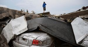 A damaged car is seen as a resident stands on top of wreckage after a tornado struck Moore, Oklahoma. Photograph: Gene Blevins/Reuters