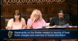 Screen grab of TDs, from left, Clare Daly, Mick Wallace and Luke 'Ming' Flanagan listening to Minister for Justice Alan  Shatter speaking in the Dáil this evening