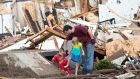 A man and two children exit a shelter after debris was cleared after a tornado struck Moore, Oklahoma last night. Photograph: Reuters
