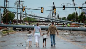 Downed utility poles block the road as a family walks south on Sante Fe Avenue in Moore, Oklahoma. Photograph: Brett Deering/Getty Images