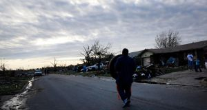 A man carries a tyre, which he found several blocks away, down the street back to his tornado-damaged house in Moore, Oklahoma.  Photograph: Rick Wilking/Reuters