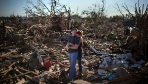 Danielle Stephan holds boyfriend Thomas Layton as they pause between salvaging through the remains of a family member's home in   Moore, Oklahoma, on the outskirts of Oklahoma City. Photograph: Adrees Latif/Reuters