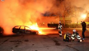 Firefighters extinguish a burning car, following riots in the Stockholm suburb of Kista. Photograph: Reuters