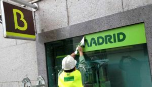 A worker removes a Caja Madrid signage to replace it with Bankia logos at a Bankia branch in Madrid this week. Photograph: Paul Hanna/Reuters