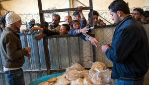 Syrian refugees wait in line for a daily bread ration distributed by the World Food Program at the Zaatari refugee camp in Jordan. Photograph: Lynsey Addario/The New York Times