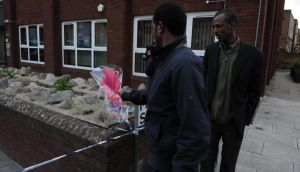 Men lay a floral tribute close to the scene where a man was murdered in Woolwich. Photograph: Nick Ansell/PA Wire