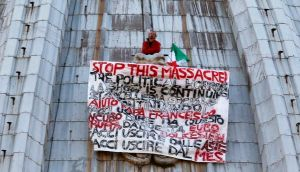 Italian businessman Marcello Di Finizio displays a banner to protest against austerity measures, on the dome of St Peter's Basilica at the Vatican. Photograph: Alessandro Bianchi