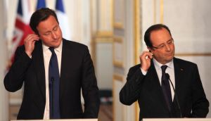 British Prime Minister David Cameron and French President Francois Hollande,  adjust their earpieces during a press conference at the Elysee Palace in Paris. Photograph: Thibault Camus/AP