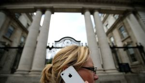 A woman on her Apple iPhone outside Government Buildings in Dublin yesterday as Taoiseach Enda Kenny reiterated that Ireland does not negotiate specific tax deals with individual companies amid mounting criticism of Apple's corporate tax arrangements and its relationship with Ireland.