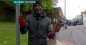 Video-grab taken from ITV News of a man holding weapons near the scene in John Wilson Street, Woolwich where a soldier was murdered. Photograph: ITV News/PA Wire
