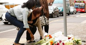 Young women lay flowers near the scene of the killing of a British soldier in Woolwich, southeast London. The soldier was hacked to death by two men shouting Islamic slogans in what British prime minister David Cameron said appeared to be a terrorist attack. Photograph: Luke MacGregor/Reuters