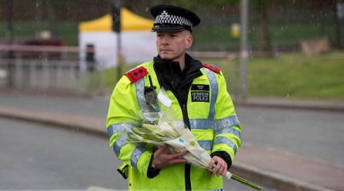 A police officer carries flowers near the scene of the killing.  Photograph: Neil Hall/Reuters