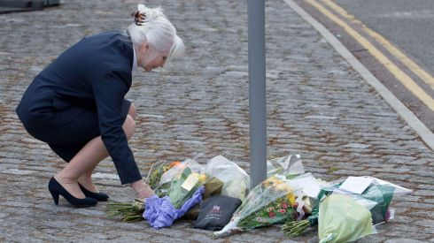 A woman lays flowers to the late soldier's memory. Photograph: Neil Hall/Reuters