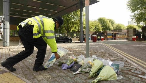 A police officer arranges floral tributes outside Woolwich barracks. Photograph: Luke MacGregor/Reuters